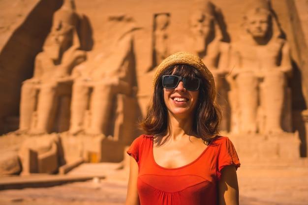 Ein junger tourist in einem roten kleid, der am abu simbel tempel in südägypten in nubien lächelt.