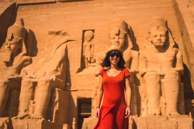 Ein junger tourist in einem roten kleid, der im abu simbel tempel lächelt
