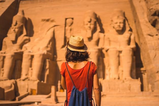 Ein junger tourist in einem roten kleid und einem strohhut, der auf den abu simbel zugeht