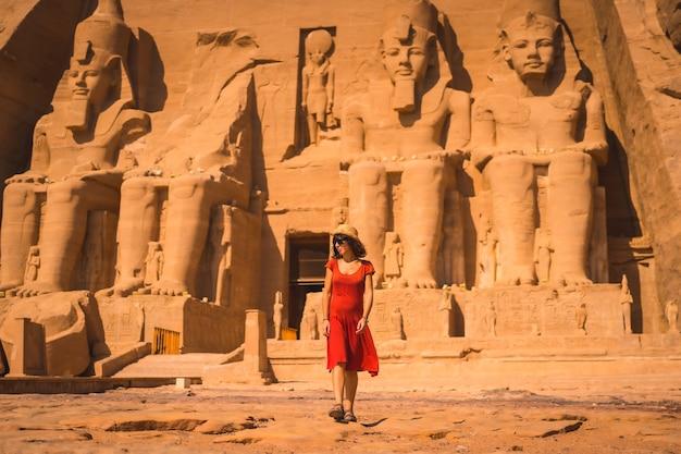 Ein junger tourist in einem roten kleid verlässt den abu simbel tempel