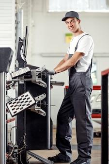 Ein junger und attraktiver mechaniker lächelt, während er mit einem computer bei einem autoservice arbeitet.