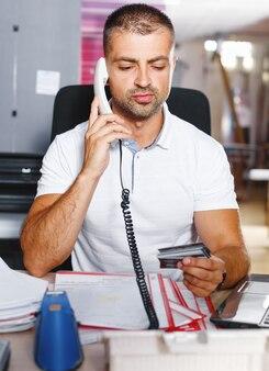 Ein junger und ehrgeiziger börsenhändler macht in einem geschäftigen büro voller computer einen deal am telefon.