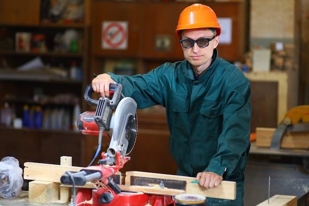 Ein junger und gutaussehender arbeiter in helm und brille arbeitet an der maschine