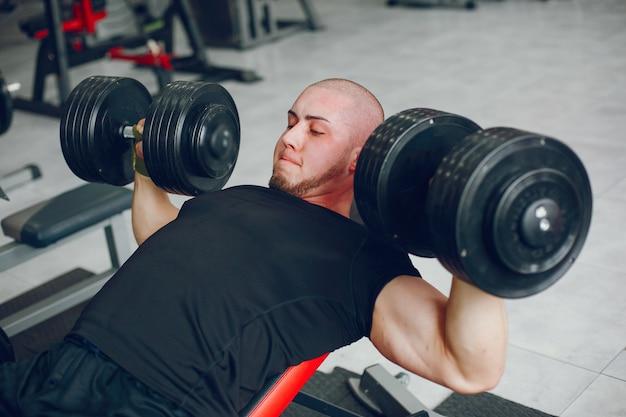 Ein junger und muskulöser kerl in einem schwarzen t-shirt bildet in einer turnhalle aus
