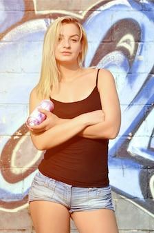 Ein junger und schöner reizvoller mädchengraffitikünstler mit einem farbenspray