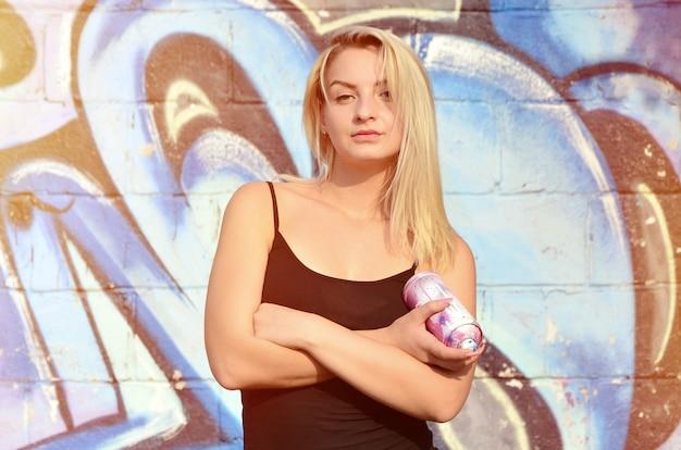 Ein junger und schöner sexy mädchengraffitikünstler mit einem farbenspray