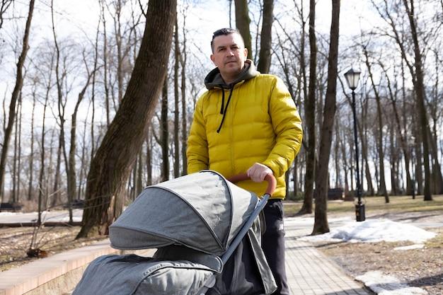 Ein junger vater geht mit seinem sohn mit einem kinderwagen im park spazieren
