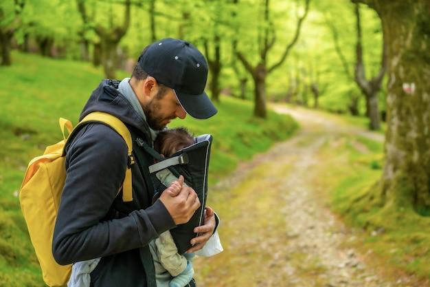Ein junger vater mit einem gelben rucksack, der mit dem neugeborenen kind im rucksack auf einem weg im wald geht