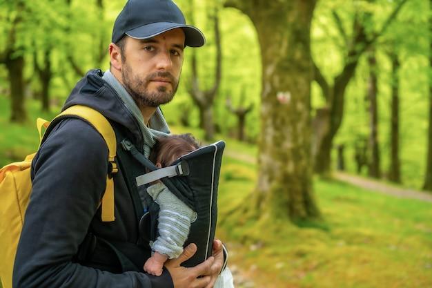 Ein junger vater mit einem gelben rucksack und einer schwarzen mütze geht mit dem neugeborenen kind im rucksack auf einem weg im wald spazieren
