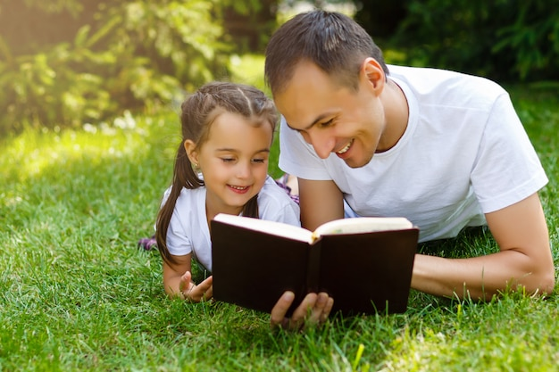 Ein junger vater mit seiner kleinen tochter liest die bibel