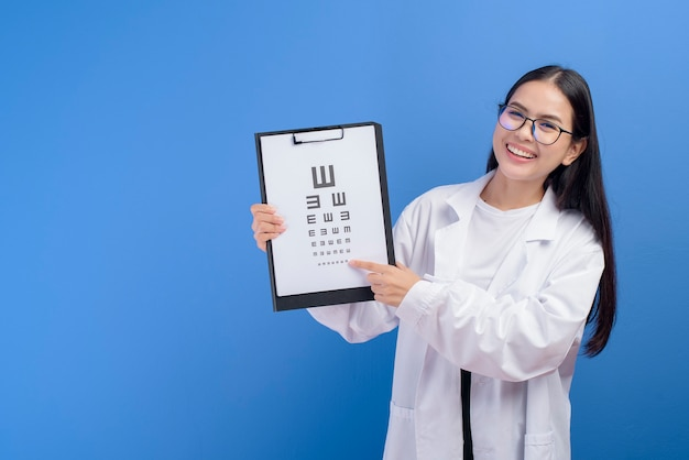 Ein junger weiblicher augenarzt mit brille, die augendiagramm über blauem gesundheitskonzept hält