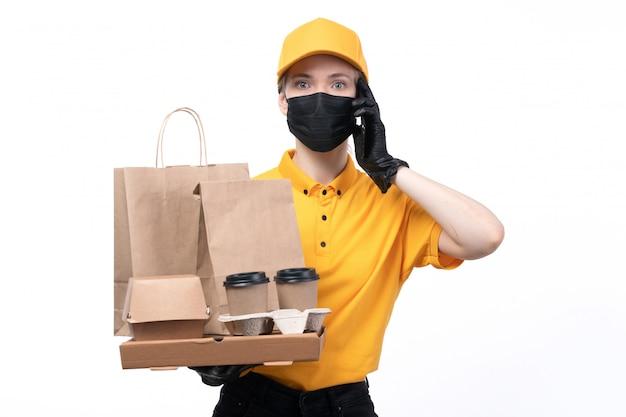 Ein junger weiblicher kurier der vorderansicht in den gelben einheitlichen schwarzen handschuhen und in der schwarzen maske, die kaffeetassen-nahrungsmittellieferungspakete halten, die am telefon sprechen