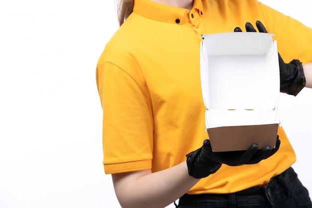 Ein junger weiblicher kurier der vorderansicht in den schwarzen glvoes der gelben uniform, die eine leere lebensmittelverpackung halten