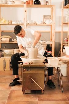 Ein junger weiblicher töpfer, der auf einer töpferscheibe in der werkstatt gestaltet
