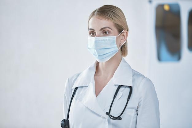 Ein junges arztmädchen setzt vor der arbeit eine schützende gesichtsmaske auf. das konzept der gesundheit