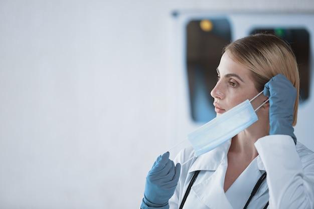 Ein junges arztmädchen setzt vor der arbeit eine schützende gesichtsmaske auf