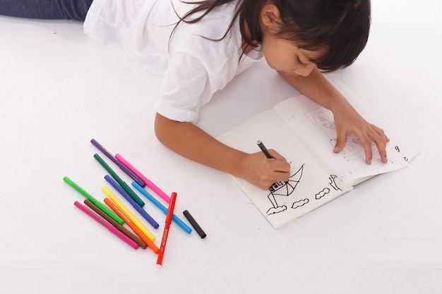 Ein junges asiatisches mädchen, das ein bild zeichnet. auf weiß