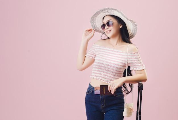 Ein junges asiatisches mädchen mit einem hellen gesicht, das einen hut trägt und eine brille trägt. halten sie einen reisepass, um im sommer im rosafarbenen hintergrund des studios zu reisen. pastellrosa-tonfilter.