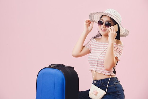 Ein junges asiatisches mädchen mit einem hellen gesicht, das einen hut und ein gepäck trägt. rufen sie an, um ein reiseticket im rosafarbenen hintergrund des studios zu buchen. pastellrosa-tonfilter.