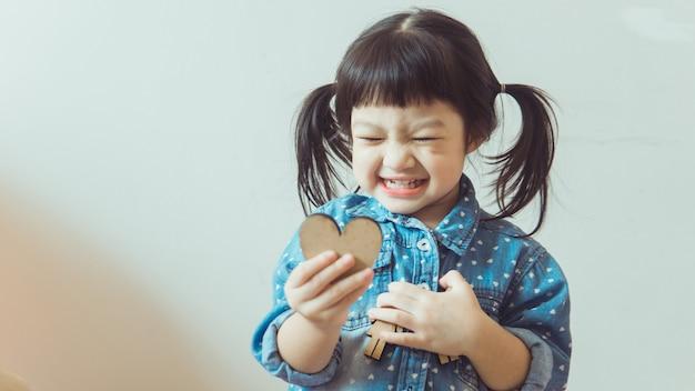 Ein junges asiatisches mädchen spielt glücklich im haus.