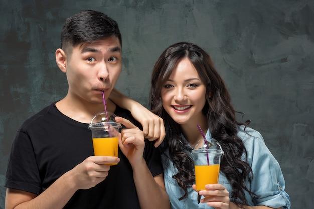 Ein junges asiatisches paar mit einem glas orangensaft