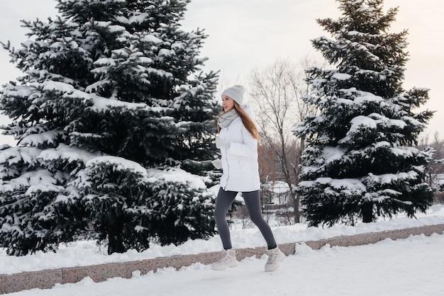 Ein junges athletisches mädchen läuft an einem sonnigen wintertag im park. eine gesunde lebensweise.