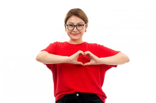 Ein junges attraktives mädchen der vorderansicht im roten t-shirt, das schwarze jeans in der sonnenbrille trägt, die sendende liebe lächelnd auf dem weiß aufwirft