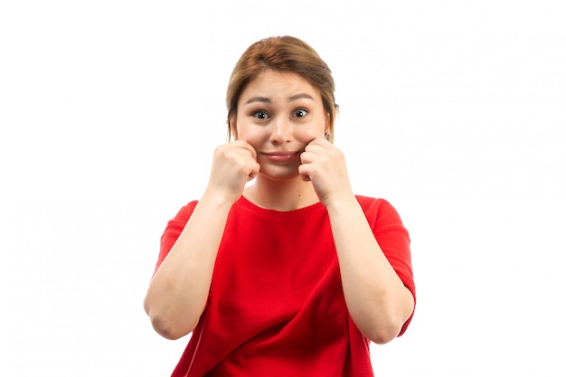 Ein junges attraktives mädchen der vorderansicht im roten t-shirt, das schwarze jeans trägt und ihre wangen auf dem weiß zieht