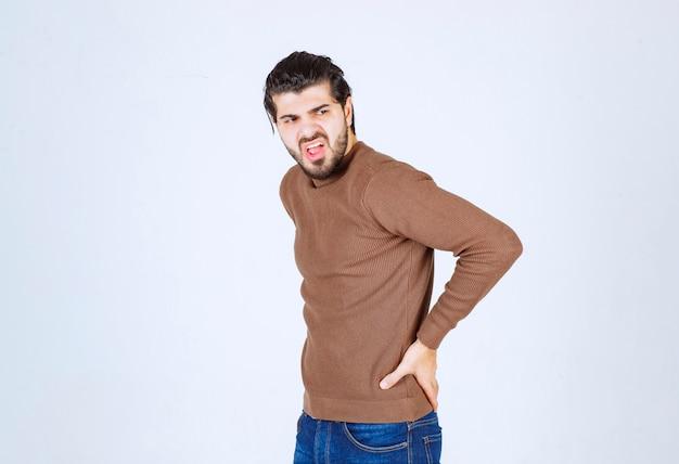 Ein junges attraktives modell in der braunen strickjacke, die über der weißen wand steht.