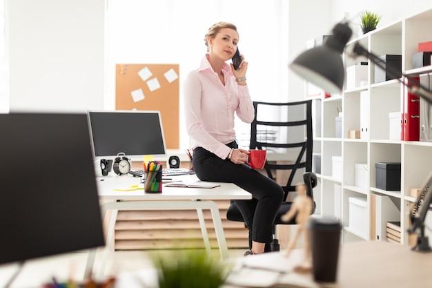 Ein junges blondes mädchen sitzt auf einem tisch im büro, hält eine rote tasse in der hand und telefoniert.