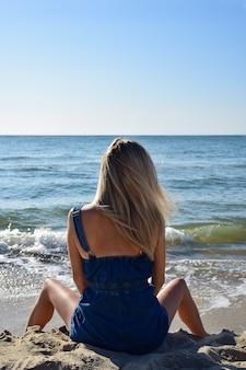 Ein junges blondes mädchen sitzt morgens mit gespreizten beinen am strand. rückansicht