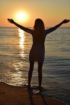 Ein junges blondes mädchen steht am strand und schaut mit ausgestreckten armen in die sonne.
