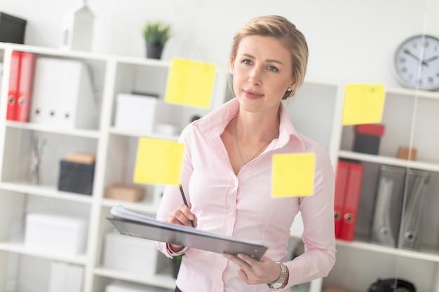 Ein junges blondes mädchen steht im büro neben einem transparenten brett mit aufklebern und hält dokumente und einen bleistift in den händen.