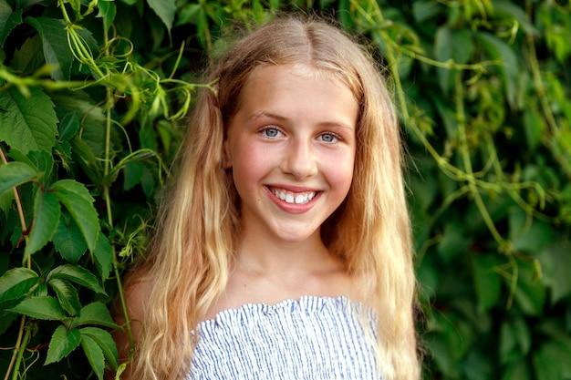 Ein junges blondes mädchen steht in den blättern wilder trauben. foto in hoher qualität