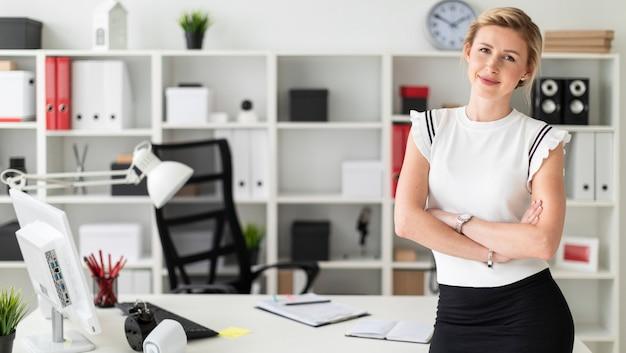 Ein junges blondes mädchen steht nahe einer tabelle im büro.