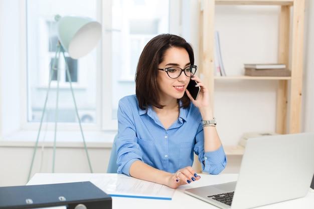 Ein junges brünettes mädchen arbeitet am tisch im büro. sie trägt ein blaues hemd und eine schwarze brille. sie spricht am telefon.
