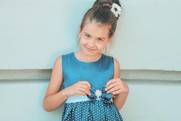 Ein junges brünettes mädchen in einem blauen kleid mit weißen tupfen steht an der wand. foto in hoher qualität