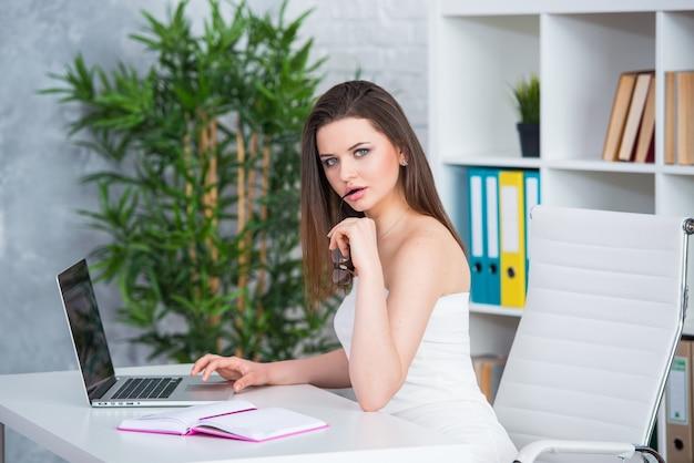 Ein junges brünettes mädchen in einem weißen kleid sitzt im büro am tisch. frau arbeitet am laptop.