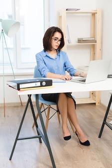 Ein junges brünettes mädchen sitzt am tisch im büro. sie trägt ein blaues hemd und schwarze schuhe. sie tippt auf einem laptop.