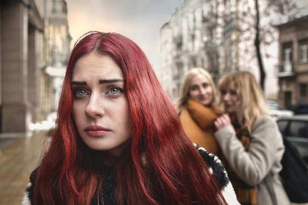 Ein junges depressives studentenmädchen mit roten haaren, das von gleichaltrigen gemobbt wird, gestört von verzweiflungsgefühlen und unterdrückung. soziale probleme