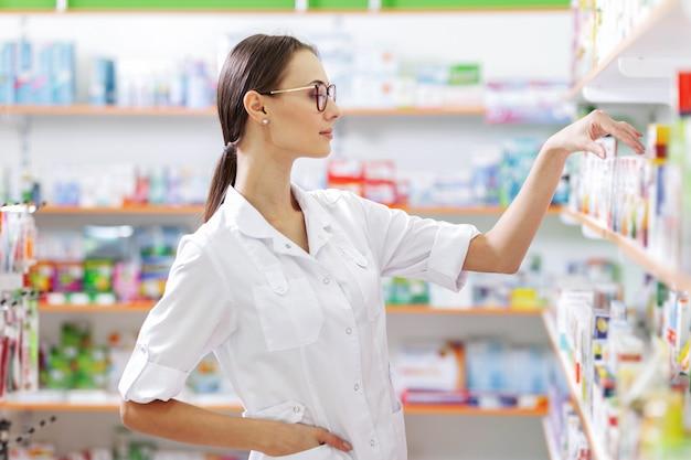 Ein junges, dünnes braunhaariges mädchen mit brille, gekleidet in einen laborkittel, nimmt in einer apotheke einige medikamente aus dem regal. das profil des mädchens wird angezeigt. .