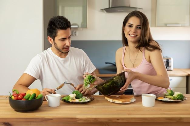 Ein junges ehepaar, das zu hause frühstückt.