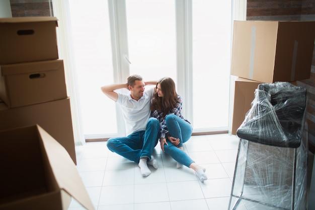 Ein junges ehepaar im wohnzimmer des hauses sitzt am fenster. sie freuen sich über ein neues zuhause. umzug, hauskauf, wohnungskonzept.