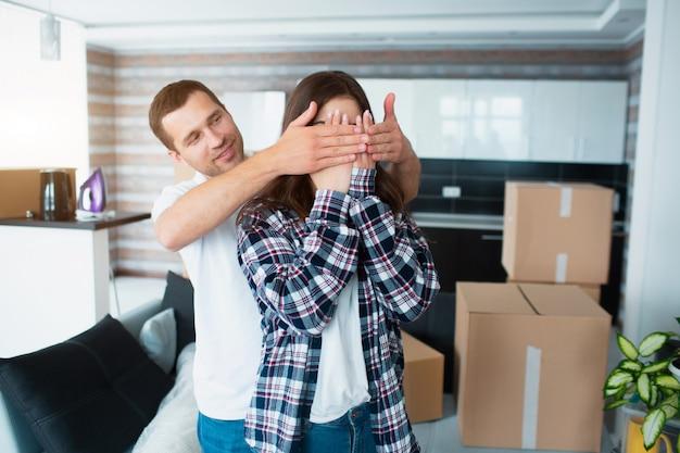 Ein junges ehepaar im wohnzimmer des hauses steht in der nähe von ausgepackten kisten.