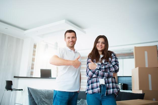 Ein junges ehepaar im wohnzimmer des hauses steht neben ausgepackten kisten, hält den daumen hoch und schaut in die kamera. sie freuen sich über ein neues zuhause. umzug, hauskauf, wohnungskonzept.