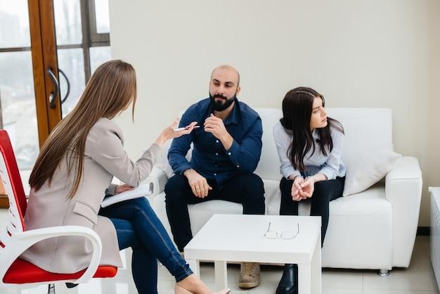 Ein junges ehepaar von männern und frauen spricht während einer therapiesitzung mit einem psychologen