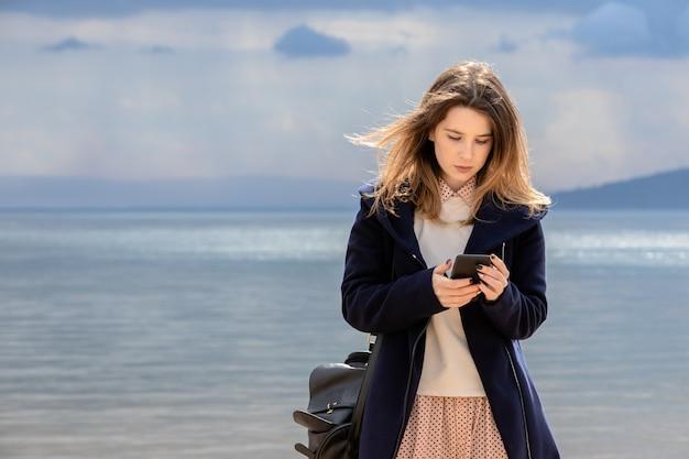 Ein junges erwachsenes mädchen mit einem smartphone steht an der küste vor einem dunklen bewölkten himmel.