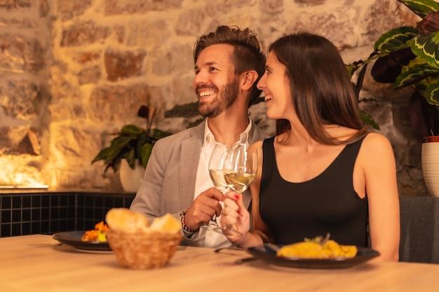 Ein junges europäisches paar, das beim abendessen in einem restaurant auf getränke röstet und valentinstag feiert