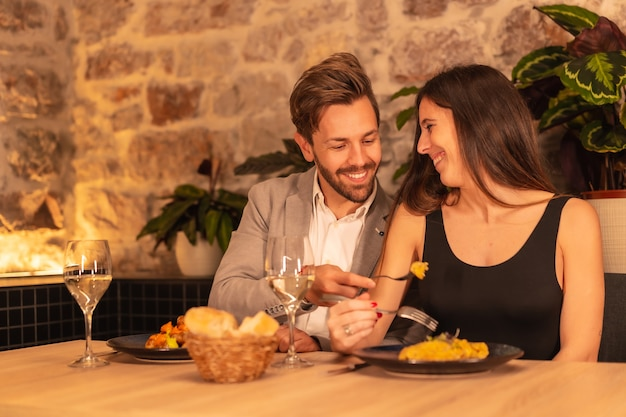 Ein junges europäisches paar in einem restaurant, das spaß daran hat, zusammen mit essen zu abend zu essen und valentinstag zu feiern
