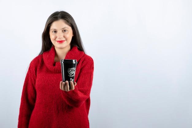 Ein junges frauenmodell im roten pullover, das eine tasse kaffee anbietet